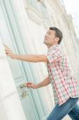 Man ringing a door bell — Stockfoto