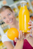 Shop assistant holding orange and juice — Stockfoto