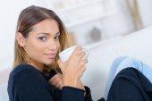 Woman having a nice coffee on the sofa — Stockfoto