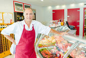 Proprietor of Deli leaning on chilled counter — Stock Photo