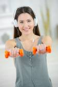 Woman lifting weights whilst listening to music — Stock Photo
