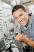 Mechanic using a drill to adjust part — Stock Photo