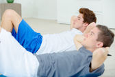 Two men doing sit-ups — Stock Photo