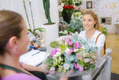 Florist serving a young lady — Stock Photo