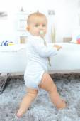Baby with dummy standing — Stock Photo