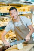 Local deli worker slicing some cheese — Stock Photo