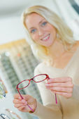 Woman holding spectacles — Stock Photo