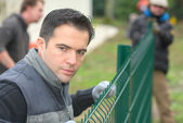 Gardening team putting up a garden fence — Stock Photo