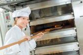 Female baker at bread oven — Stock Photo