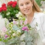 Florist holding a flower arrangement — Stock Photo #77596590