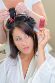 Lady passing curler to hairdresser — Stock Photo