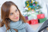 Woman using a laptop by her Christmas tree — Stock Photo