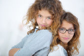Two young girls stood back to back — Stock Photo