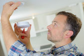 Fitting a smoke alarm to be safe — Stock Photo
