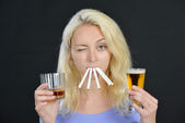 Blond woman both  smoking and drinking — Stock Photo