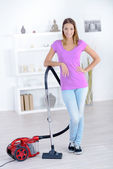 Woman stood with a vacuum cleaner — Stock Photo