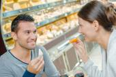 Couple eating meal, holding cheeses — Stock Photo
