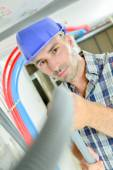 Electrician working through an open ceiling hatch — Stock Photo
