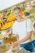Lady weighing produce in paper bag — Stock Photo