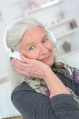 Senior lady wearing headphones — Stock Photo