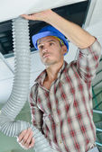 Electricians working in a ceiling hatch — Stock Photo