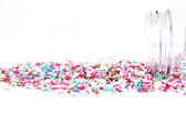 Spilled sprinkles with container on white background — Stock Photo