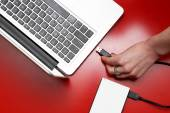 Top view of female hand connecting external hard drive to laptop — Stock Photo