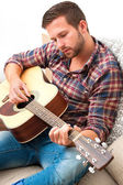 Musician playing acoustic guitar — Stock Photo