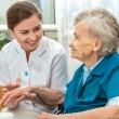 Elderly woman is assisted by nurse at home — Stock Photo #52342117