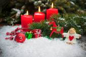 Red candles burning  in snow for third advent — Stock Photo
