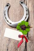 Horseshoe and four leaf clover with empty tag — Stockfoto