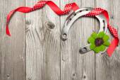 Horseshoe, shamrock and red ribbon on old wooden — ストック写真