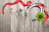 Horseshoe, shamrock and red ribbon on old wooden — Stock fotografie