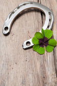 Horseshoe with a shamrock on old wooden — Stock fotografie