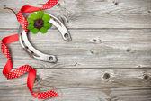 Horseshoe, shamrock and red ribbon on old wooden — Stock Photo