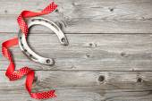 Horseshoe with red ribbon on old wooden — Stock Photo