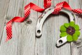Horseshoe, shamrock and red ribbon on old wooden — 图库照片