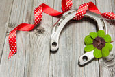 Horseshoe, shamrock and red ribbon on old wooden — Stockfoto
