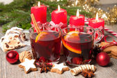 Red mulled wine on table with burning candles — Stock Photo