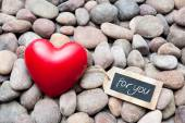 Red heart on pebble stones with tag — Foto Stock