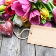 Bouquet of tulips with an empty tag and red heart — Stock Photo #63579323