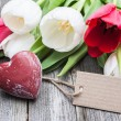 Bouquet of tulips with an empty tag and red heart — Stock Photo #63579537