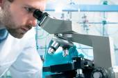 Scientist looking through a microscope — Stock Photo