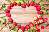 Frame of fresh roses with a gift box — Stock Photo
