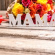 Bunch of roses with a gift box and word Mama — Stock Photo #67646577