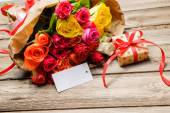 Bunch of roses and gift box with an empty tag — Stock Photo