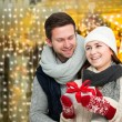 Happy young couple with Christmas present — Stock Photo #74651559