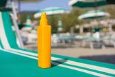 Protection solaire crème sur lit de bronzage sur la plage — Photo