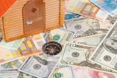 Plastic house on a pile of money — Stock Photo