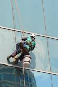 A worker cleaning windows service on high rise building — Stock Photo